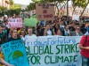 """Hundreds of protesting young people march behind a sign saying """"Global strike for climate change"""""""