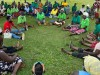 A group of people sit in a circle outside on grass.