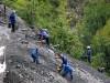 Miners on a steep hillside mine tungsten
