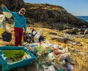 A beautiful coastline but, in the foreground, a woman is sorting a huge pile of plastic bottles