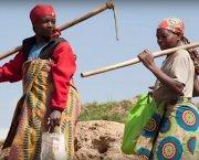 Two women carrying farming tools