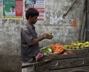 A vegetable seller with a food truck peels a cucumber