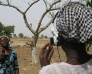 Two women in an African landscape: one with a camera filming another with a microphone
