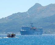 A fishing boat and cruise liner cross paths outside Zakynthos Harbour (Photo: Robert Wallace, Creative Commons, via Flickr)