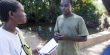 A researcher speaks to a cotton farmer in Mozambique.