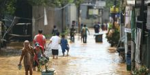 Citizens wade through a flooded road in Bandung City