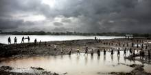 Men form a human chain to carry mud up to the embarkment. They are trying to build a new and stronger flood barrier after Cyclone Aila destroyed the old one