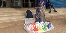A woman sitting on steps, with colourful handkerchiefs arranged in front of her