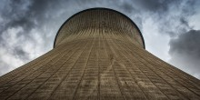 A cooling tower of a power station is framed against the sky