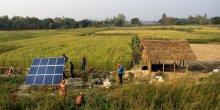 People installing solar panels in a field