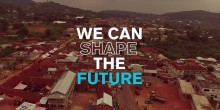 """Aerial view of poor community. Overtext reads """"We can shape the future"""""""