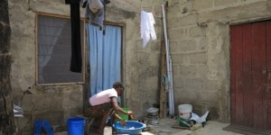 Woman washing dishes in a bowl outside.