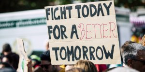 """A handwritten sign is help up saying """"Fight today for a better tomorrow"""""""