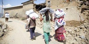 Women carrying emergency shelter kits