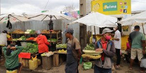 Market traders wearing face masks sell produce