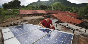 Indian woman does maintenance work on solar panel, with mountains in the background.