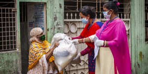 Women delivering a package to another woman, all wearing face masks.