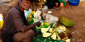 Jack fruit vendor spreads out their wares on the ground.