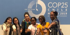 Smiling women gather in front of a climate change conference sign and give a thumbs up