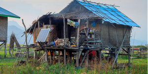 A solar panel outside a rural house on stilts