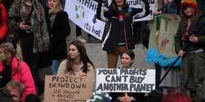 """A group of young women protestors with placards, one reading """"Your profits can't buy another planet"""""""