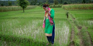 A woman farmer holds a phone to her ear in a green field.