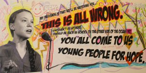 """An image of youth climate leader Greta Thunberg on a mural, with her speech: """"You all come to us young people for hope. This is all wrong"""""""