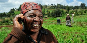 A farmer standing in a field holds a mobile phone to her ear