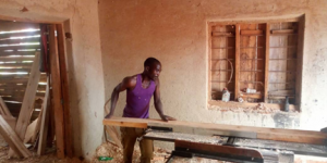A carpenter uses a jointer powered by a mini-grid