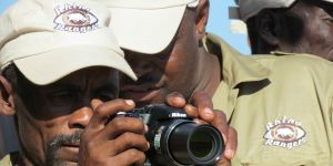 A man peers through the lens of a camera, while receiving advice from his colleague, another ranger