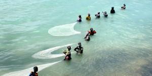Women fishing in shallow water