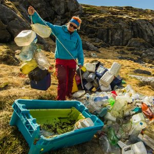 A beautiful coastline but in the foreground, a woman is sorting a huge pile of plastic bottles