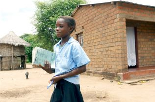 The daughter of Charles, a former mukula logger, leaves for school. Charles' income from mukula supported his daughter's education in the last few years