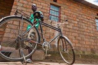 Andrew stands proudly next to the bicycle he bought with money from mukula trade