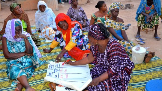 A group of women writing notes on a poster.
