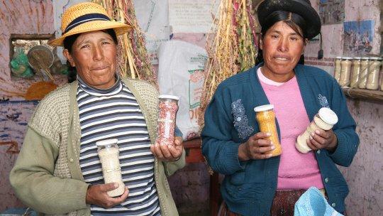 Two women holding jars of quinoa