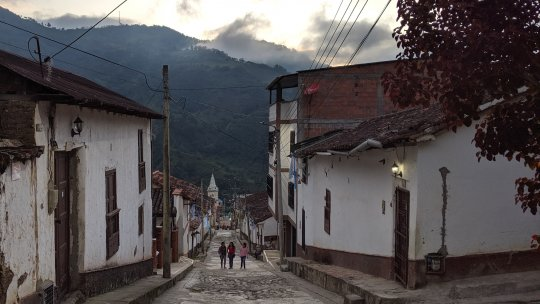 People walking down a street with mountains in the background