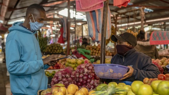 A man buying fresh fruit at a market stall.