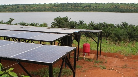 Solar panels on the ground next to a lake.