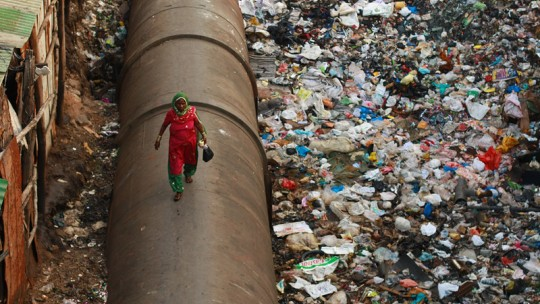 Woman walking on a pipe with garbage around.