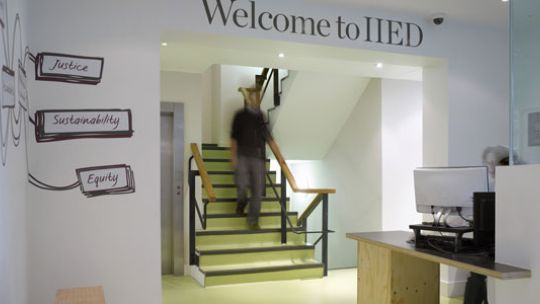 A man descends some stairs in the reception area of the IIED office, below a sign saying 'Welcome to IIED'
