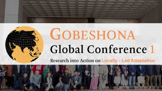 """A group of people pose for a picture, behind words that say """"Gobeshona Global Conference 1"""""""