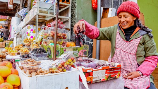 A stall-holder measures her produce in a marketplace (Photo: Hivos Bolivia)