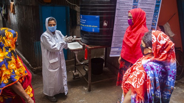 A woman covered in protective plastic and wearing a mask demonstrates handwashing to other women outside