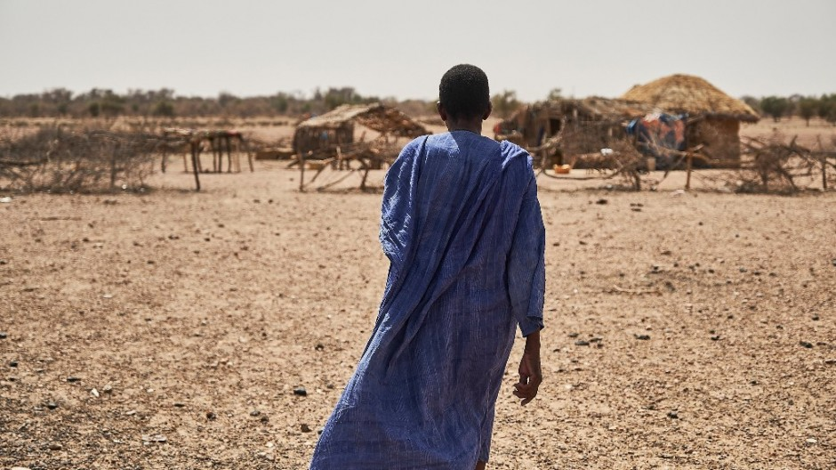 Man, wearing a blue tunic, stands with his back to the camera and looks at huts in the background.