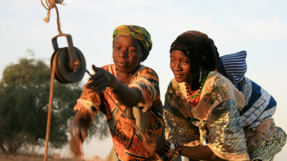Two women draw water from a well